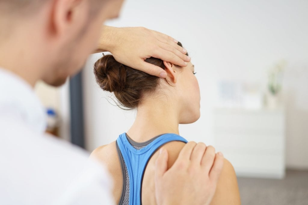 woman having her neck stretched in physical therapy